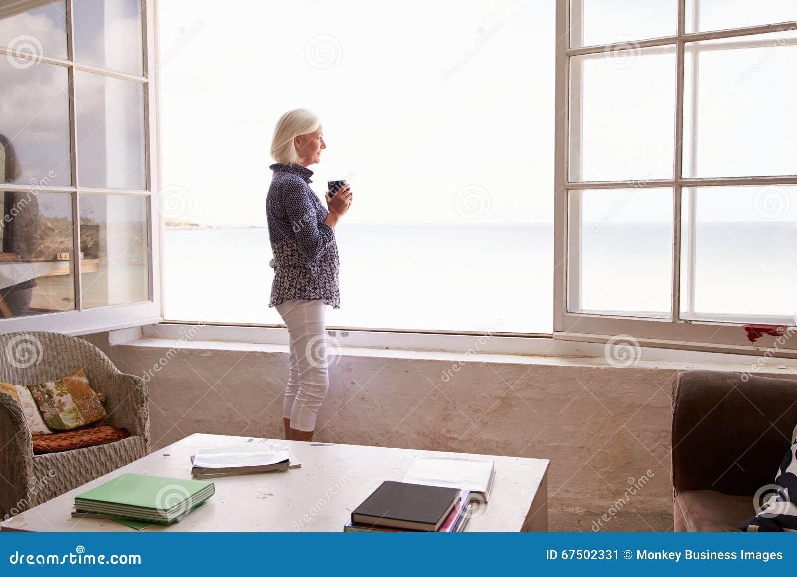 站立在窗口和看美好的海滩视图的妇女