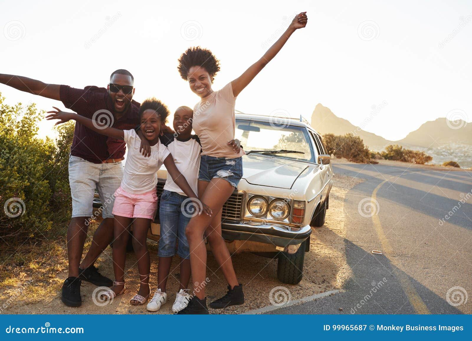 站立在经典汽车旁边的家庭画象