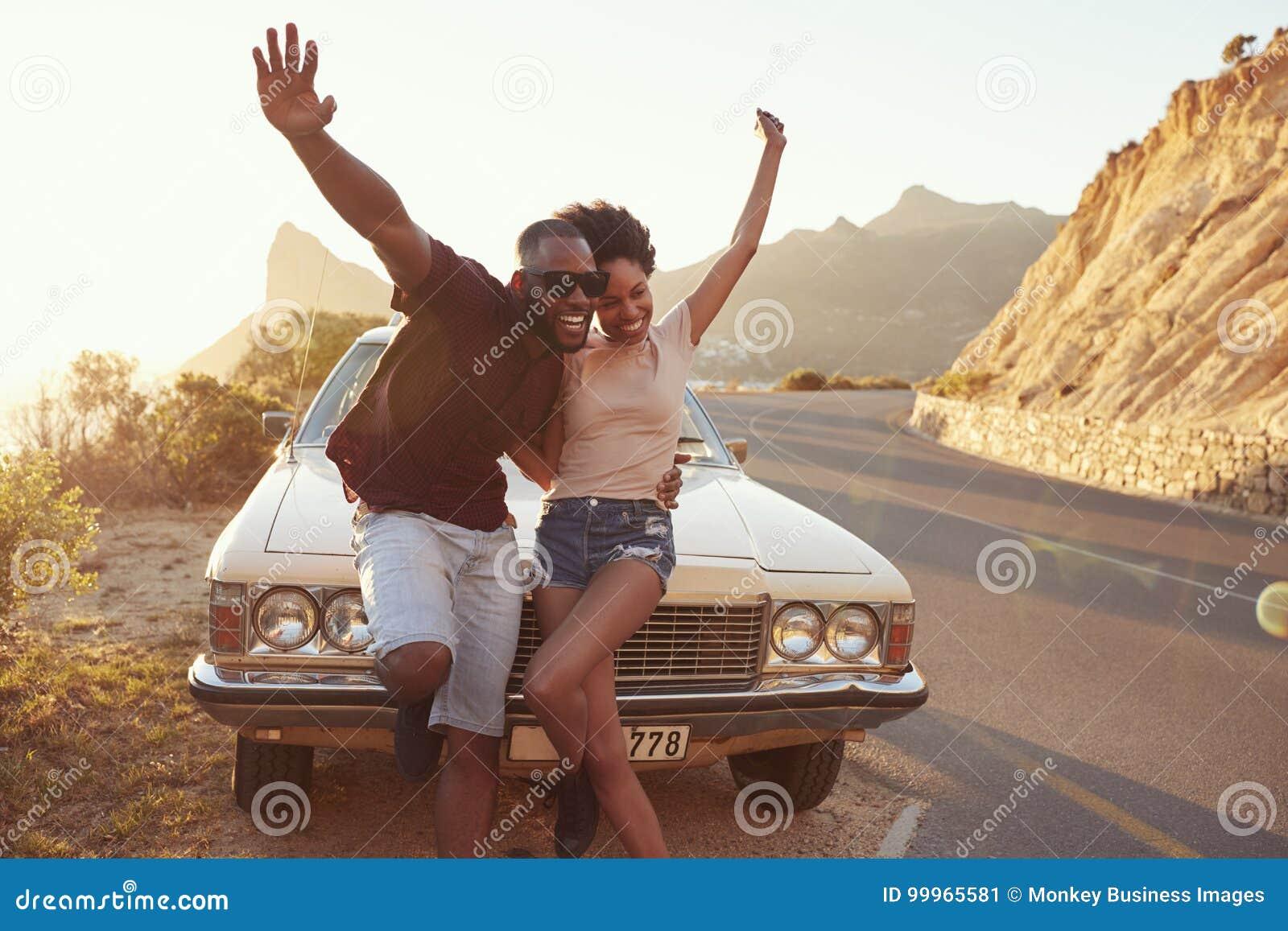 站立在经典汽车旁边的年轻夫妇画象