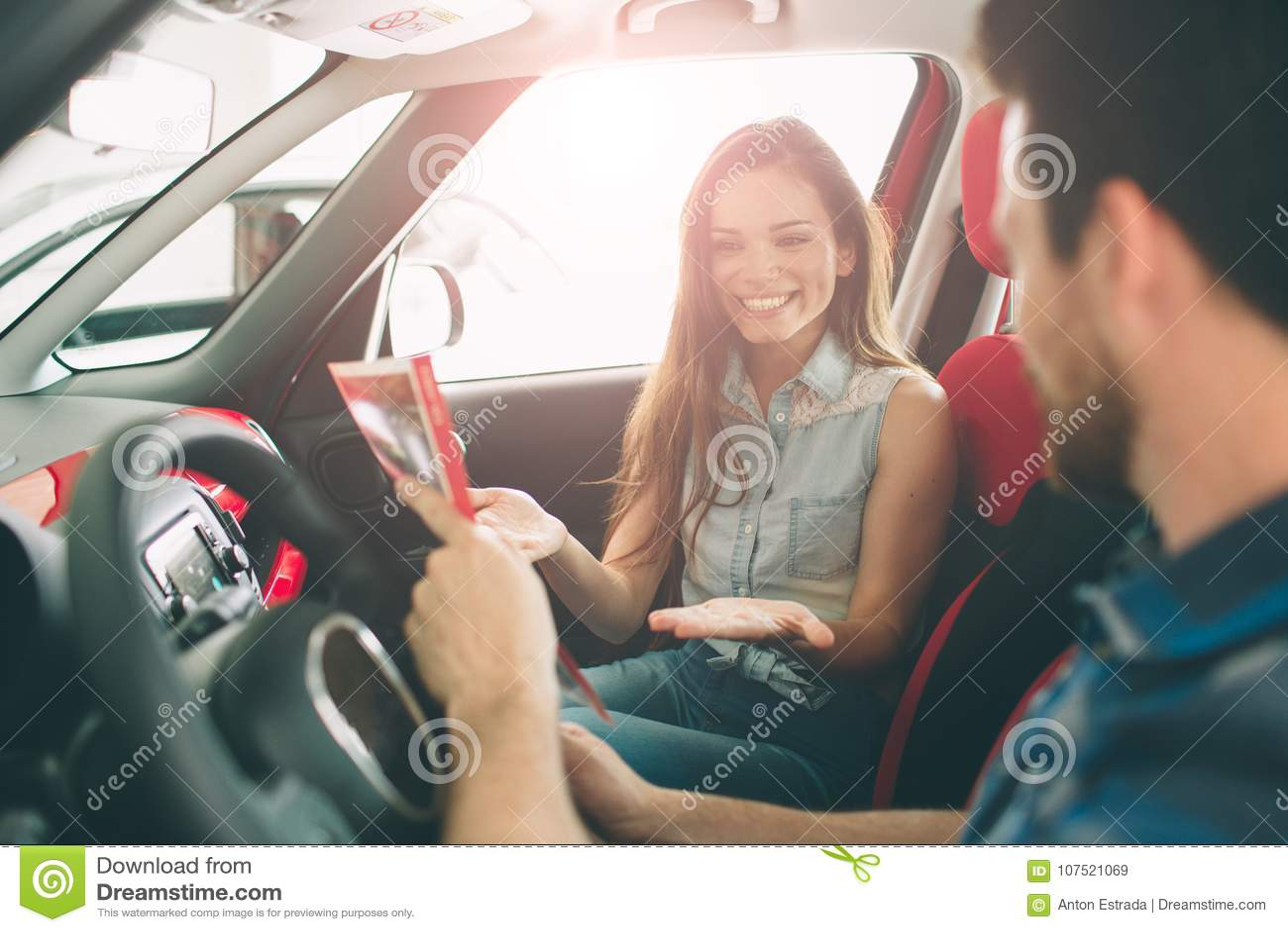 站立在经销权的美好的年轻夫妇选择汽车买