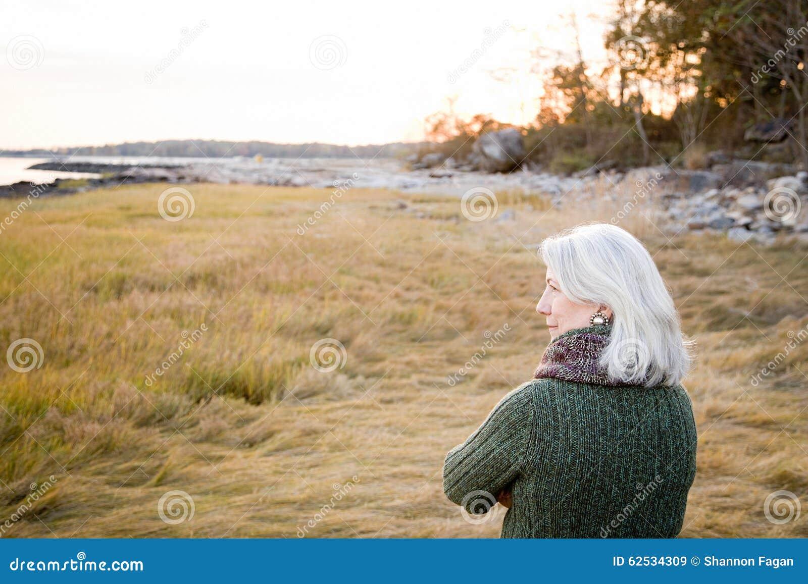 站立在草的妇女在海岸附近