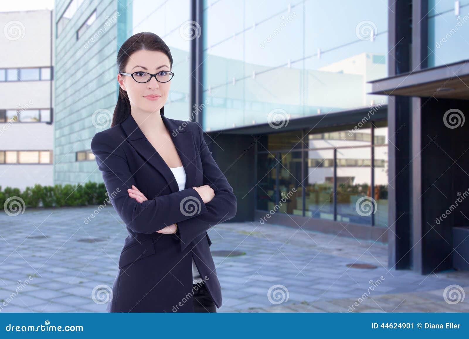 站立在街道上的女商人反对办公楼