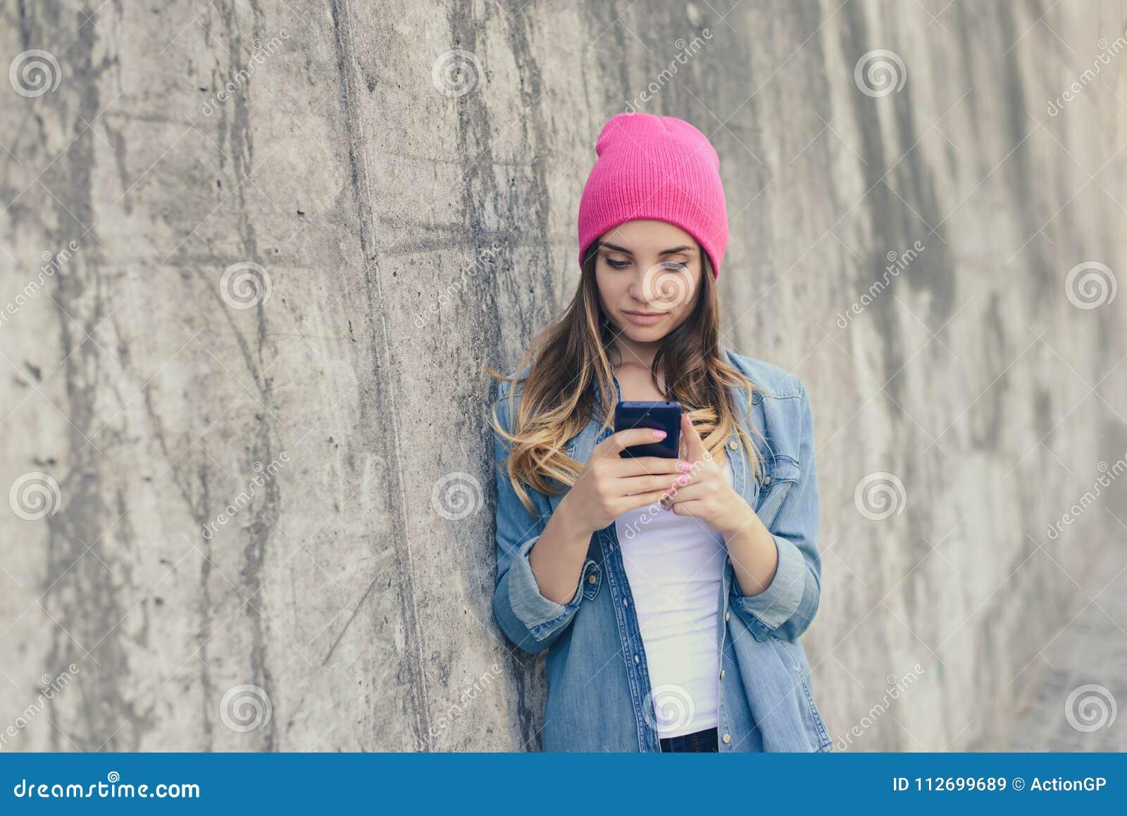 站立在街道上的近的墙壁和使用她的智能手机的便衣的逗人喜爱的美丽的女孩为通信在int中