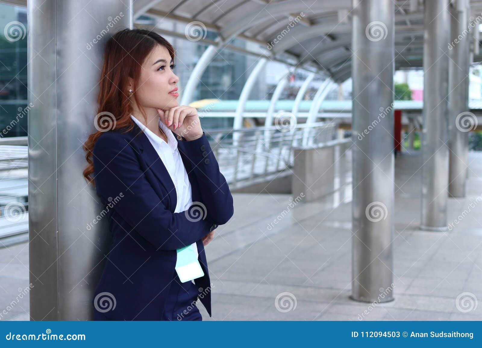 站立在边路和很远看的确信的年轻亚裔女实业家画象  认为和体贴的企业骗局