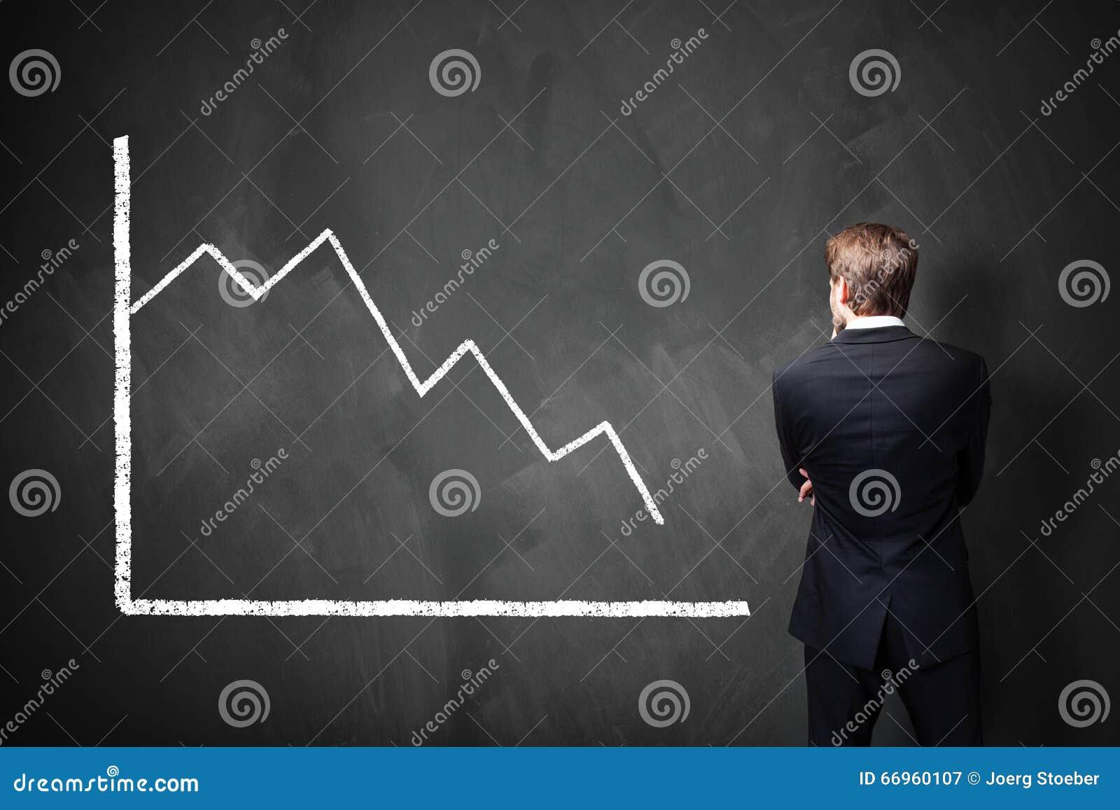 站立在黑板的一张越来越少的图前面的商人