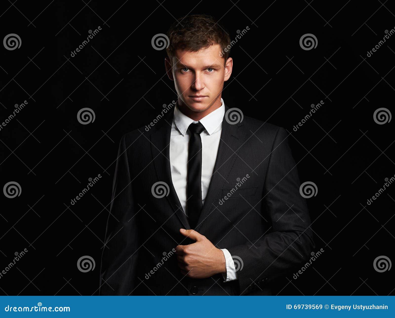 站立在黑背景的商人 grunge英俊的人摄影样式诉讼都市年轻人