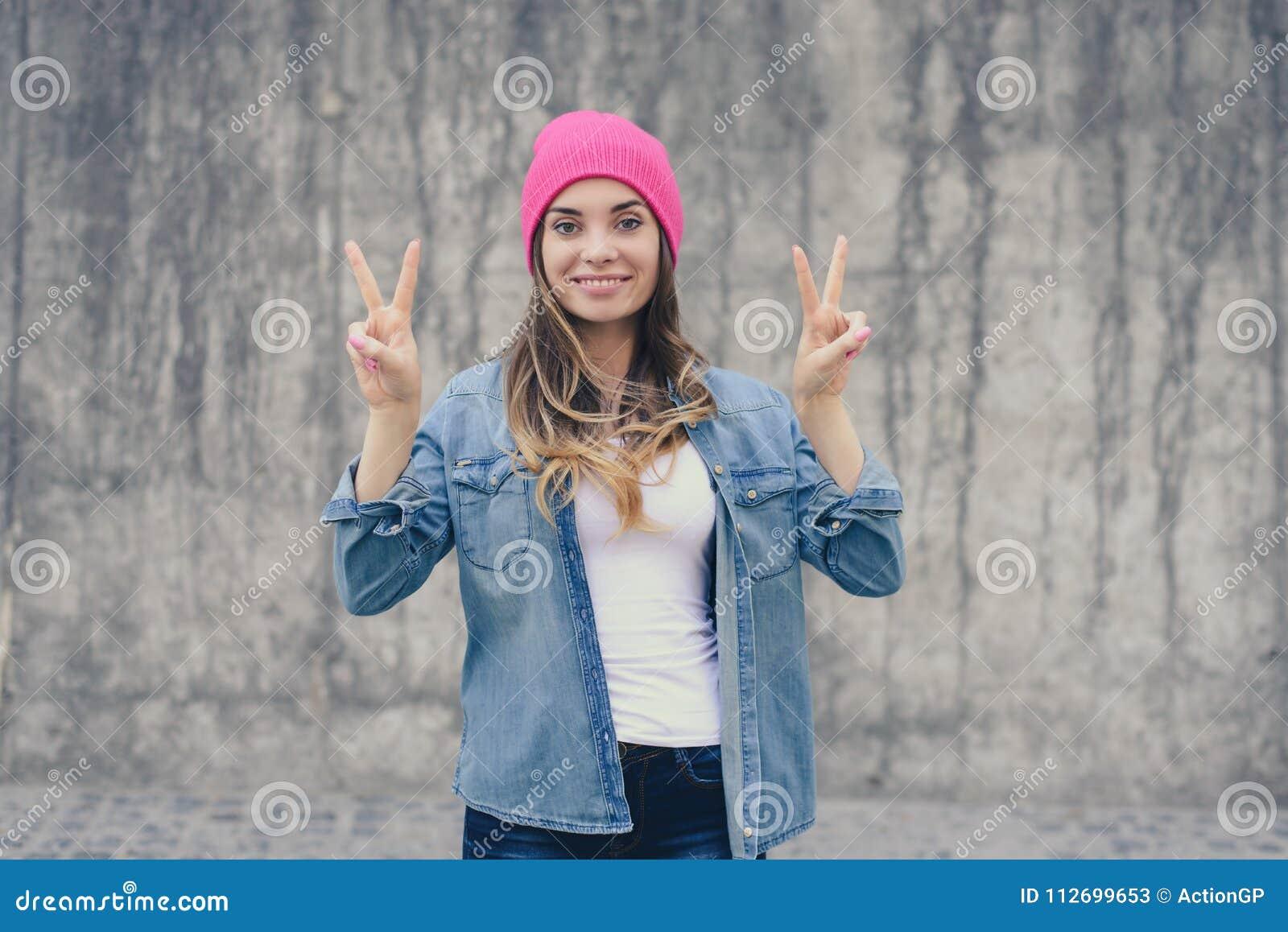 站立对灰色墙壁和显示胜利标志, v标志的便衣和桃红色帽子的愉快的快乐的微笑的行家女孩, gest