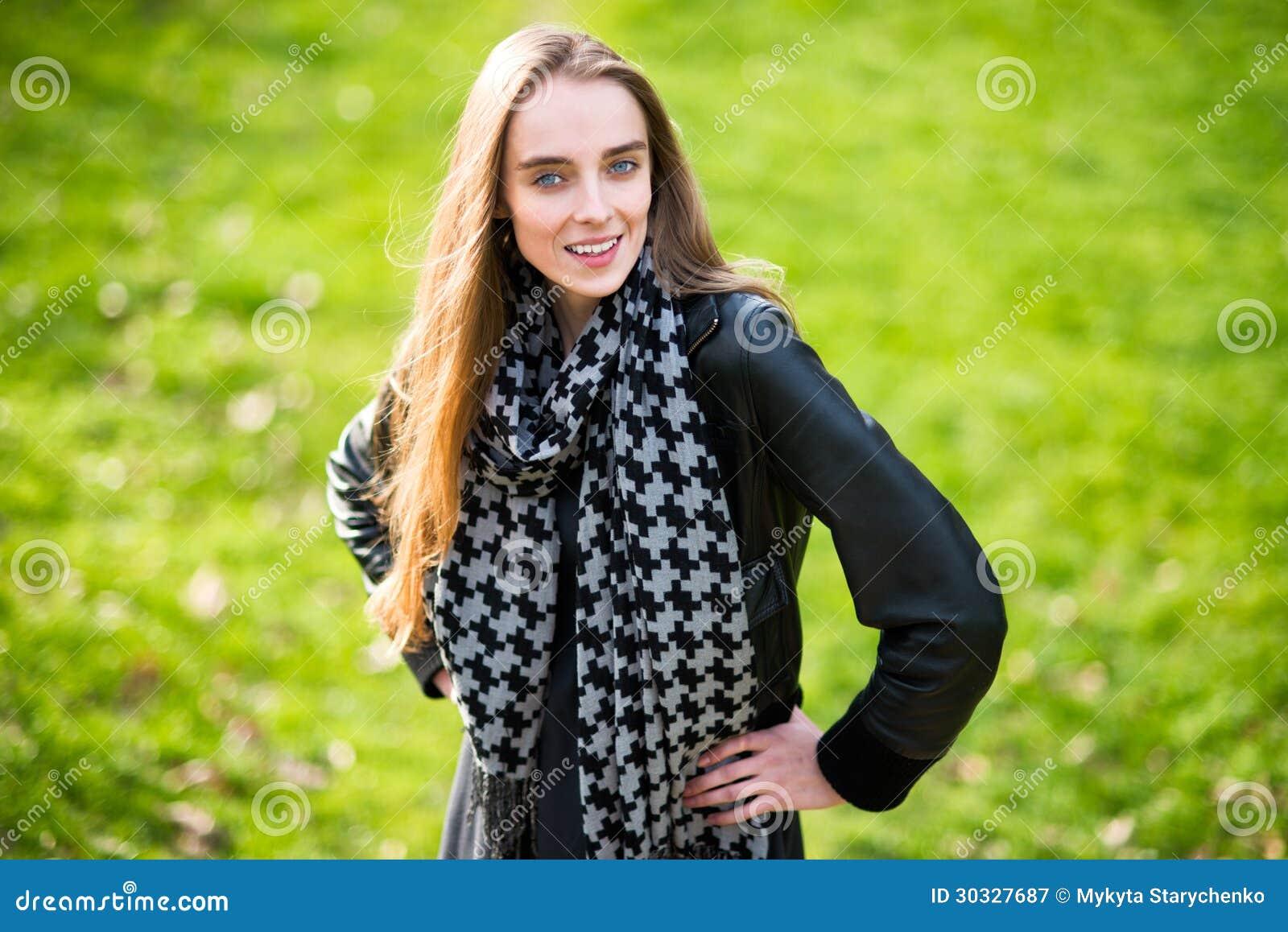 站立户外在绿草的美丽的愉快的妇女
