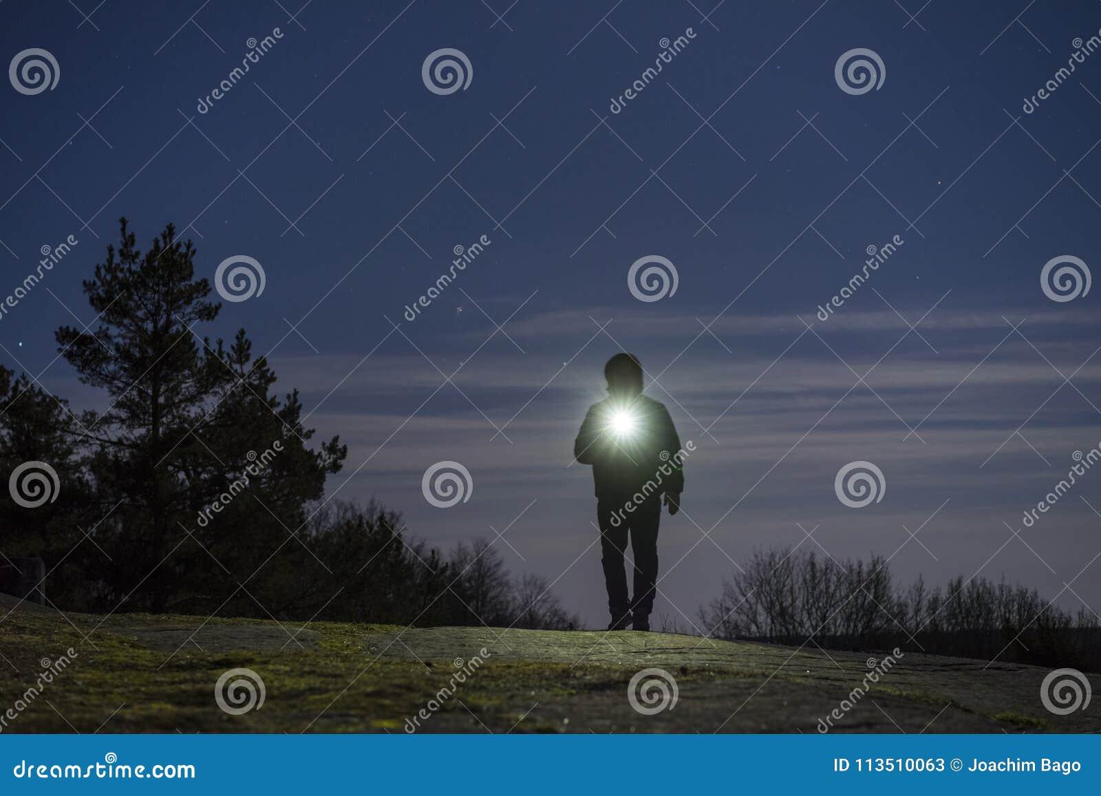站立的人室外在与手电和有冠乌鸦的晚上在头