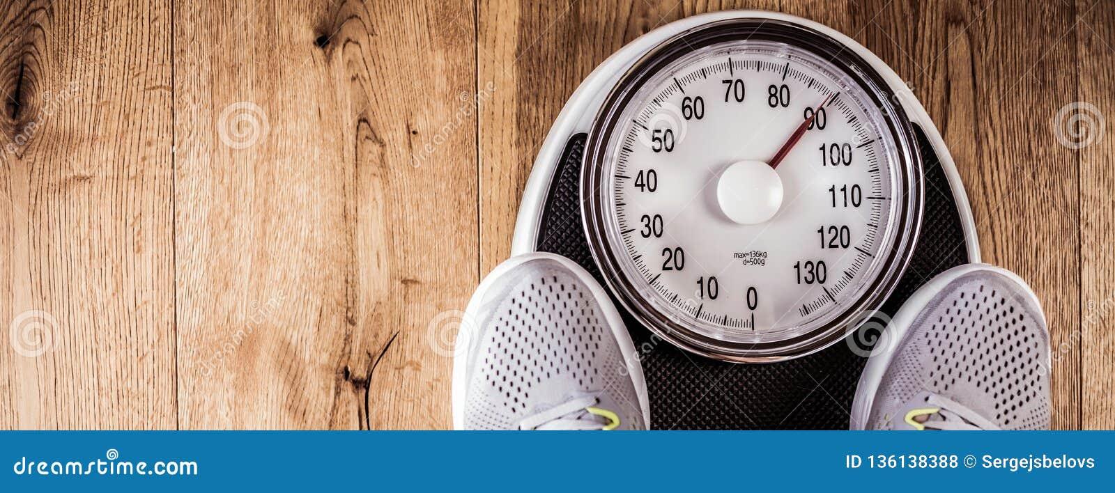 站立的人称标度在健身房 由卷尺的腰围尺寸 概念健康生活方式