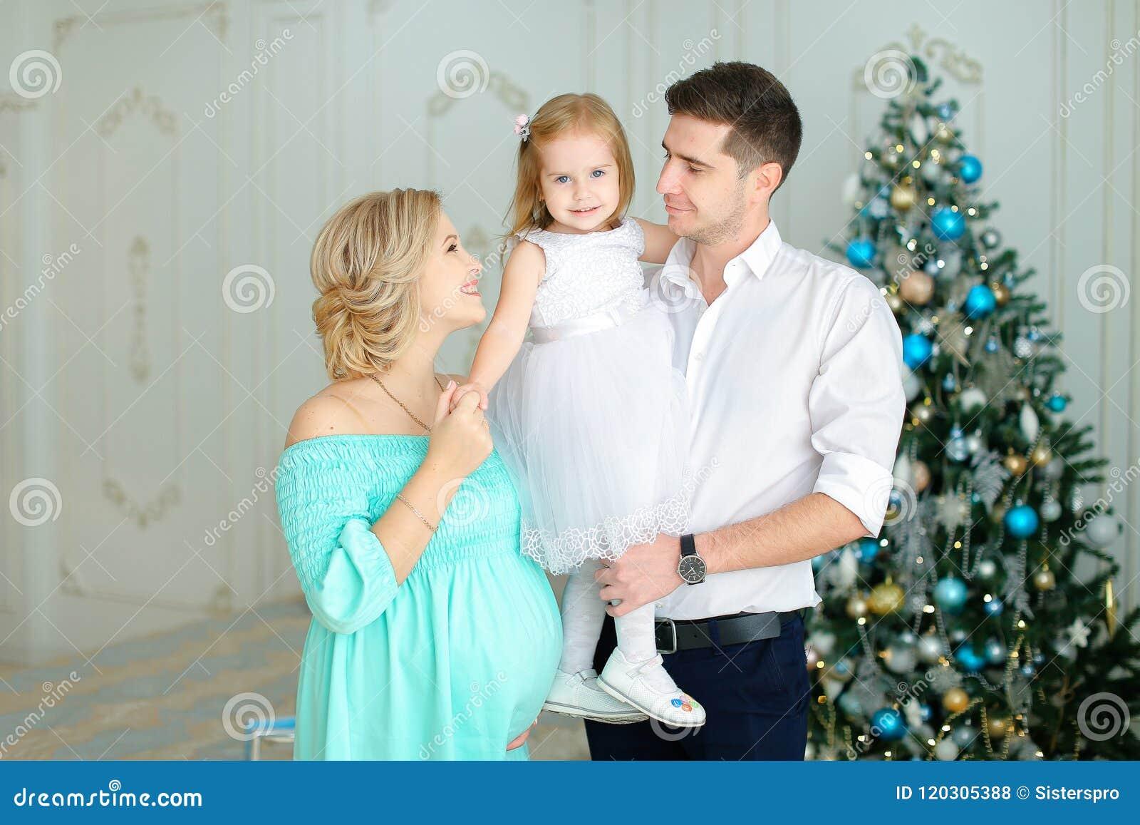 站立近的丈夫的怀孕的欧洲妇女保留小女儿在圣诞树附近