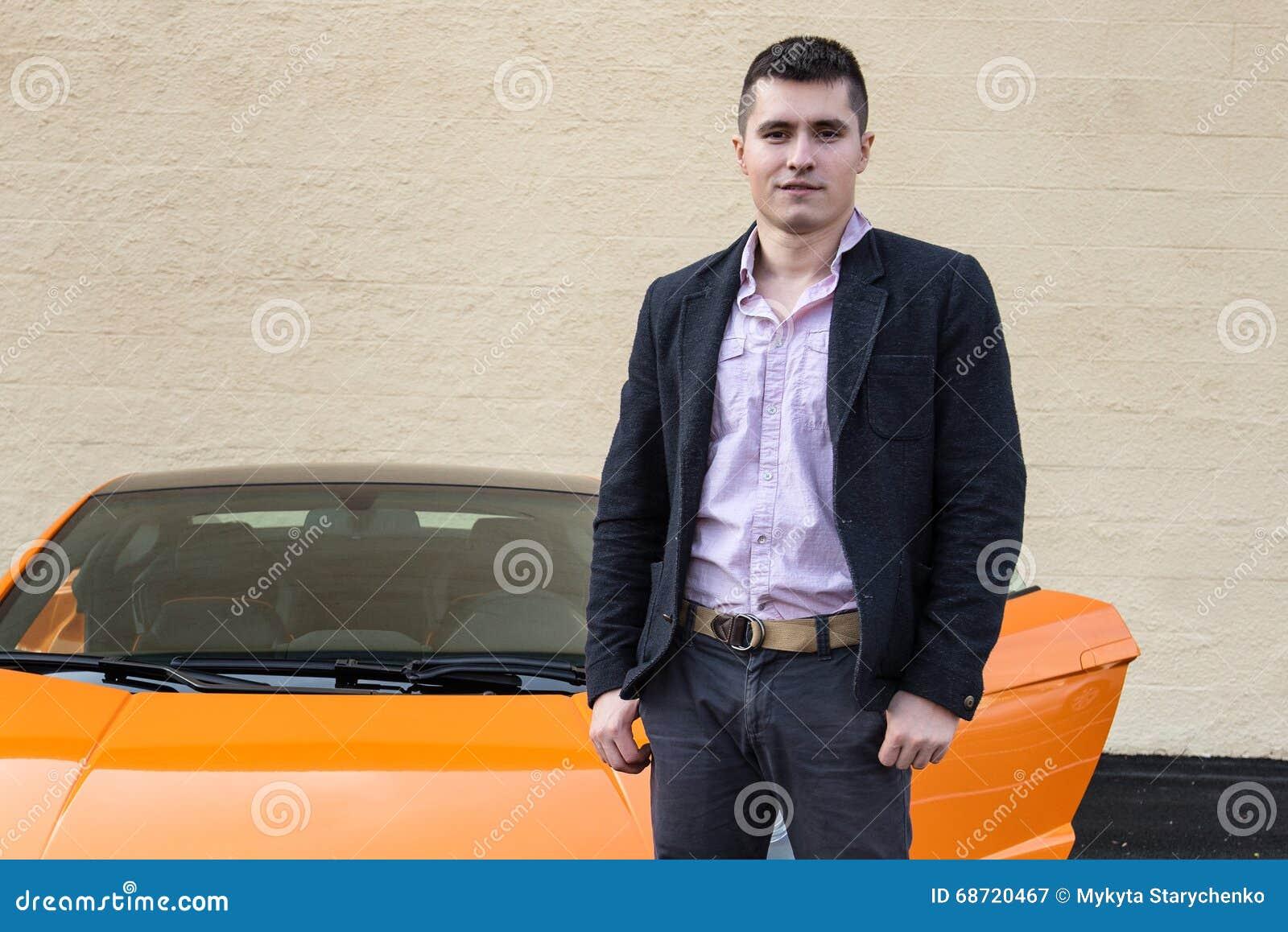 站立近的豪华跑车的年轻愉快的人