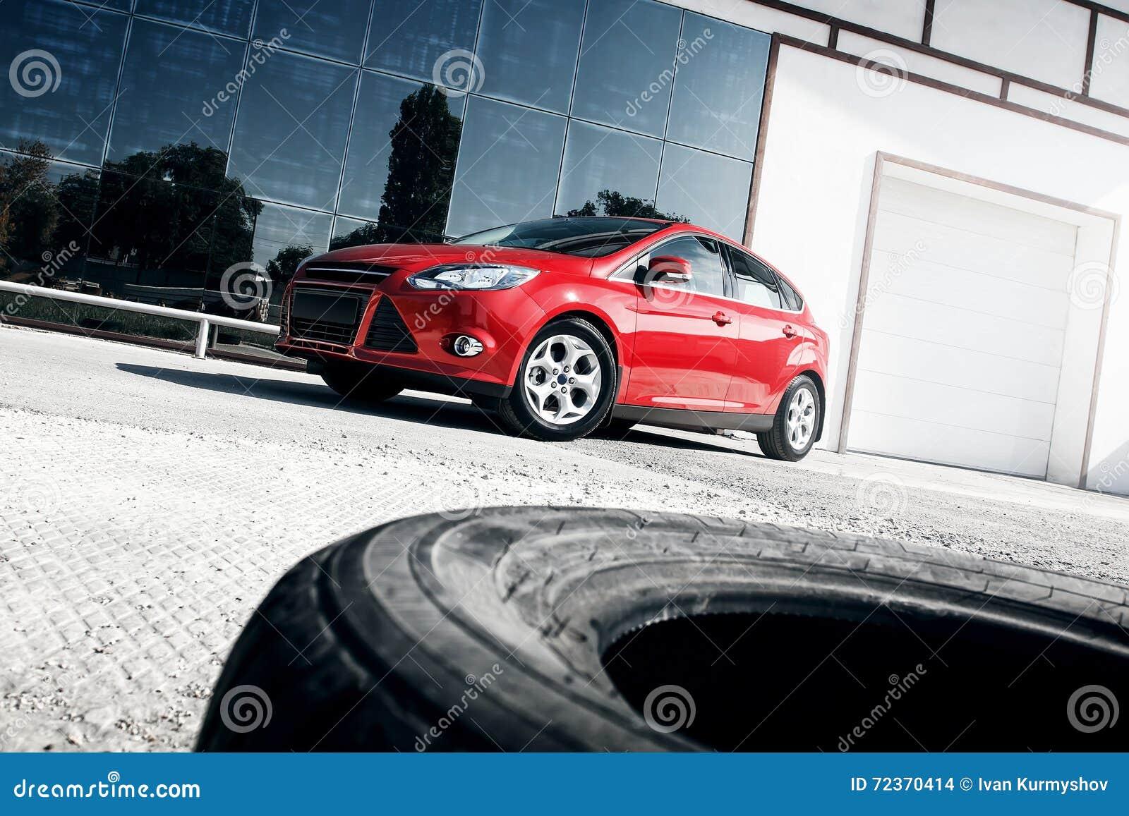 站立近的镜子修造的红色汽车