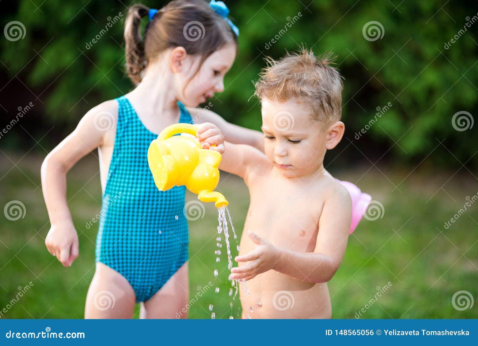 童年与水池的夏天比赛 白种人兄弟和姐妹戏剧用飞溅塑料玩具喷壶倾吐的水,