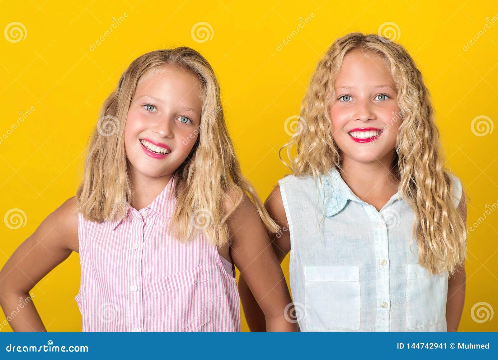 笑与完善的微笑的愉快的微笑的俏丽的少年孪生女孩 人们、情感、青少年和友谊概念 r