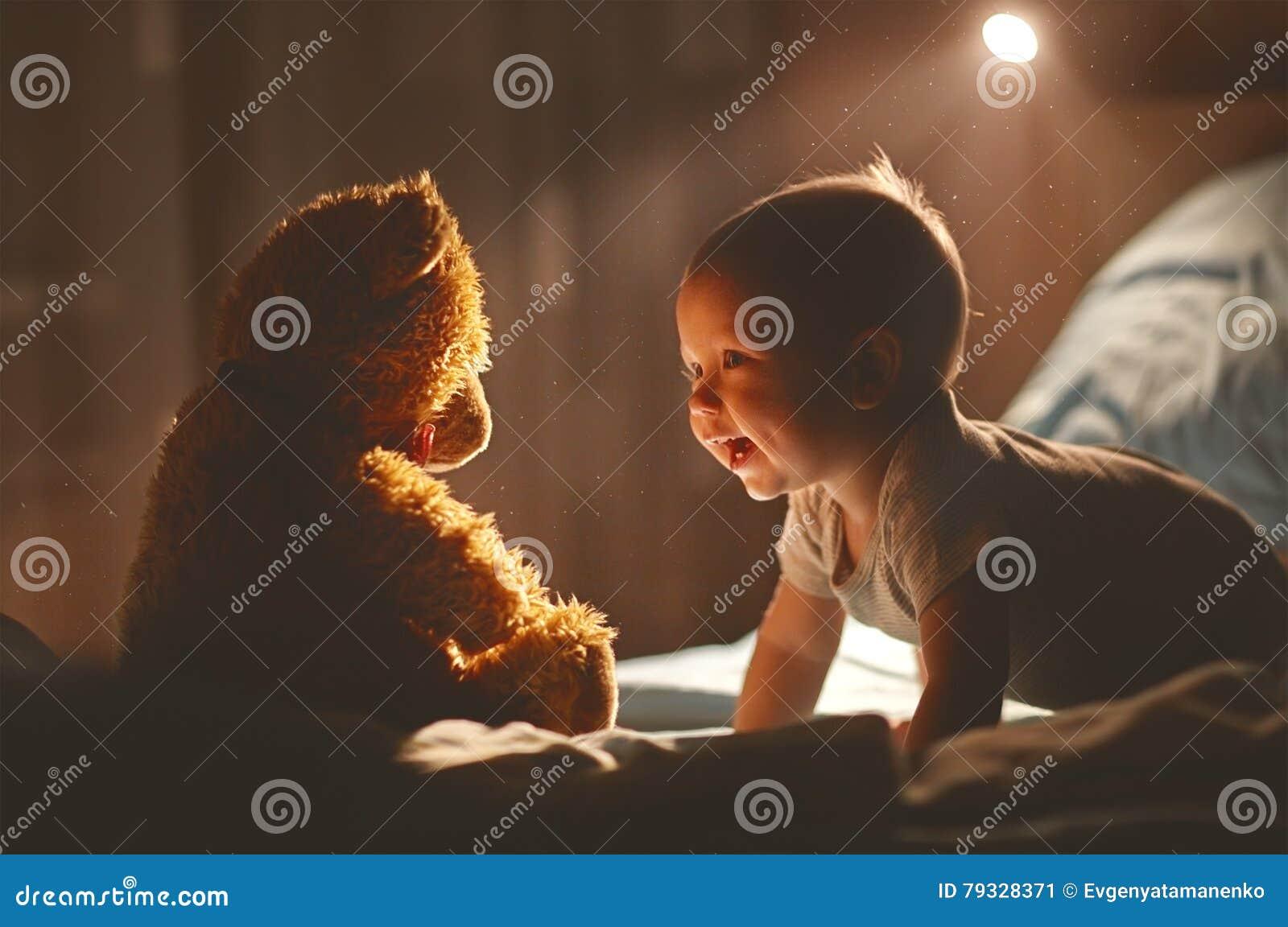 笑与玩具熊的愉快的婴孩在床上