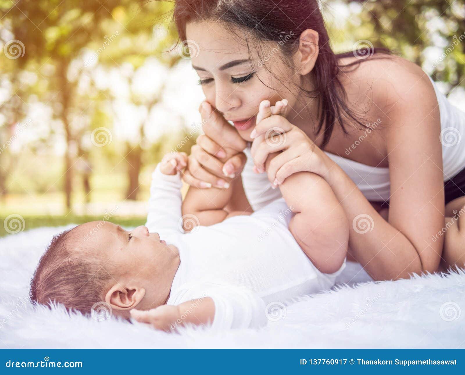 笑和使用在夏天的幸福家庭、母亲和小婴孩在公园
