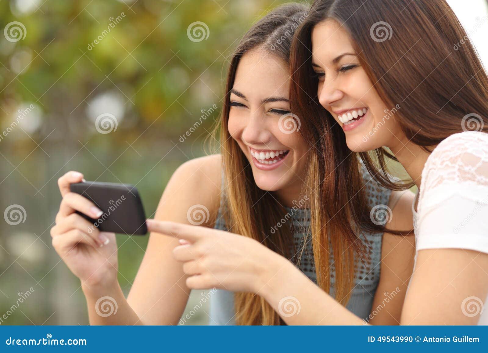 笑和分享在一个巧妙的电话的两个滑稽的妇女朋友媒介
