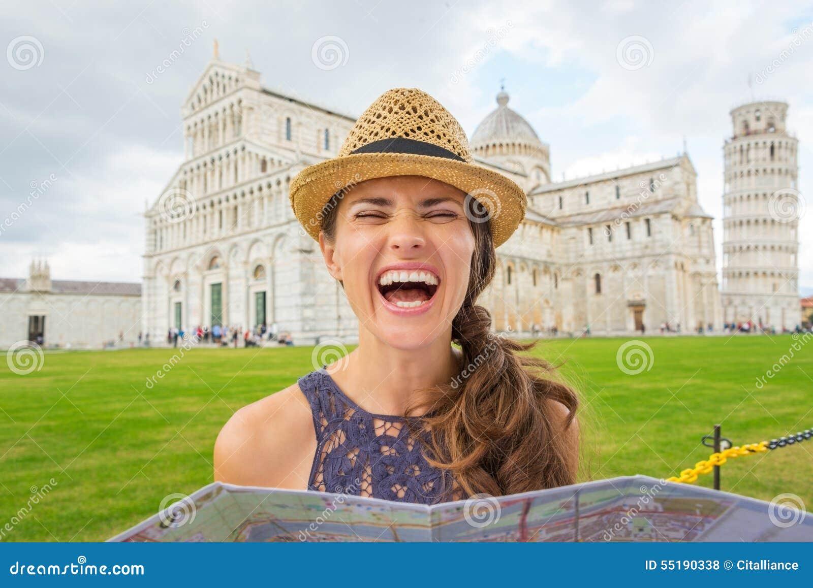 笑的妇女旅游举行的地图在比萨斜塔附近