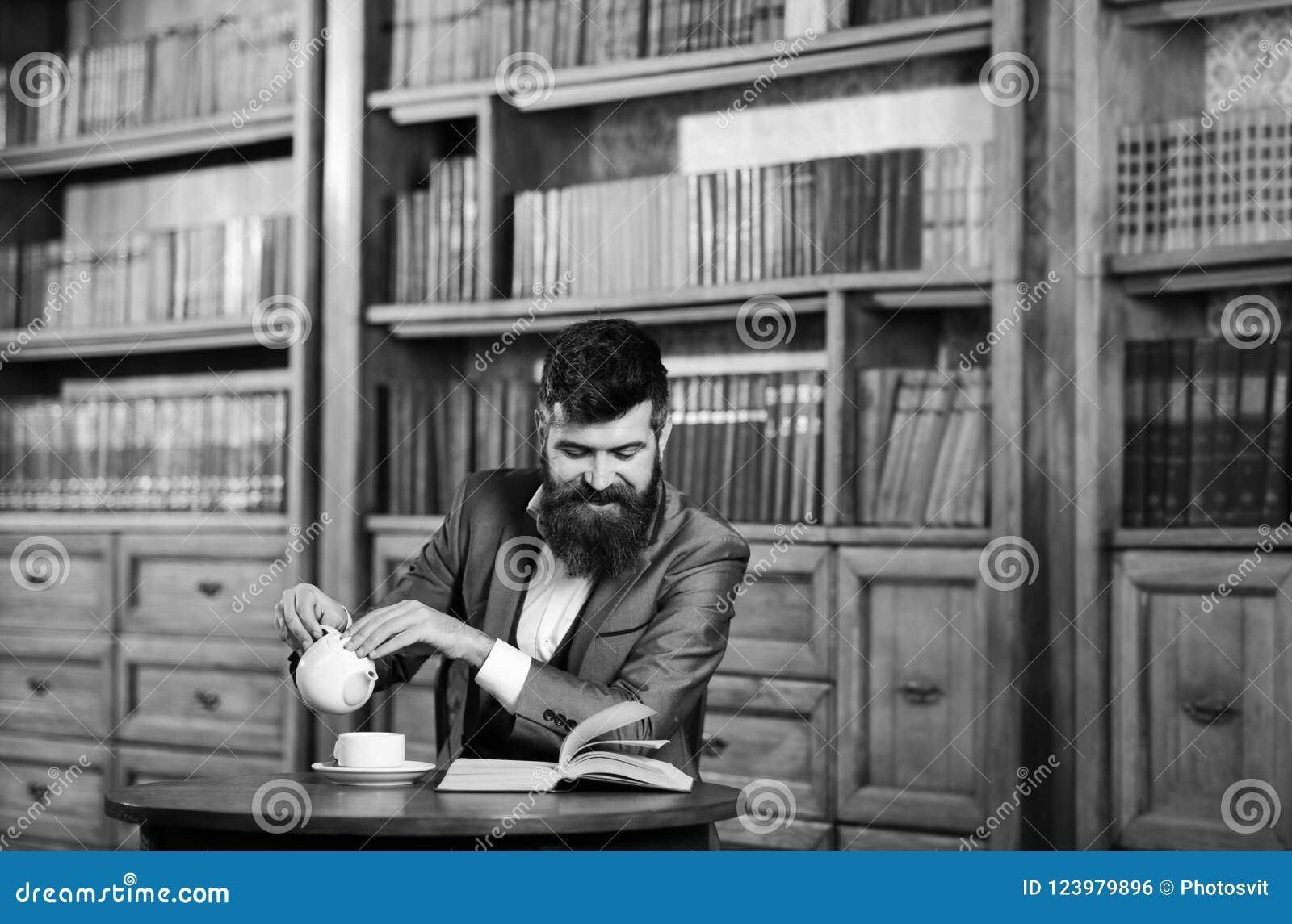 笑,放松,乐趣,休闲,爱好概念 愉快的人在内部的葡萄酒坐并且享受松弛读书 博若莱红葡萄酒