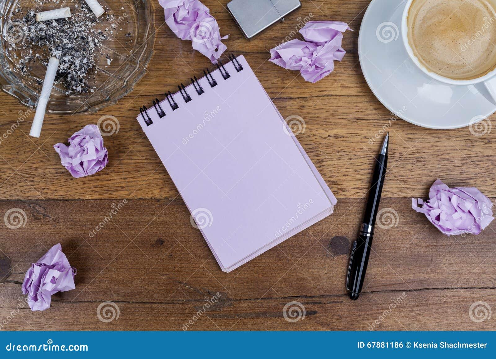 笔记本笔咖啡烟灰缸香烟弄皱了在木桌上的纸