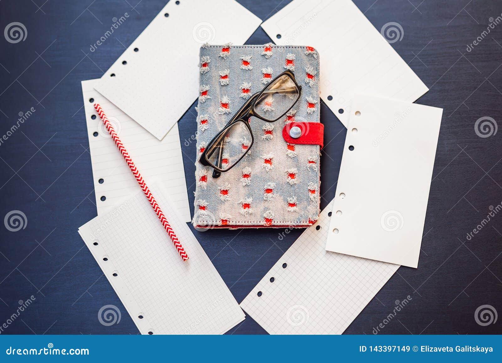 笔记薄和文具在黑背景 事务和研究的计划者 文具爱好者