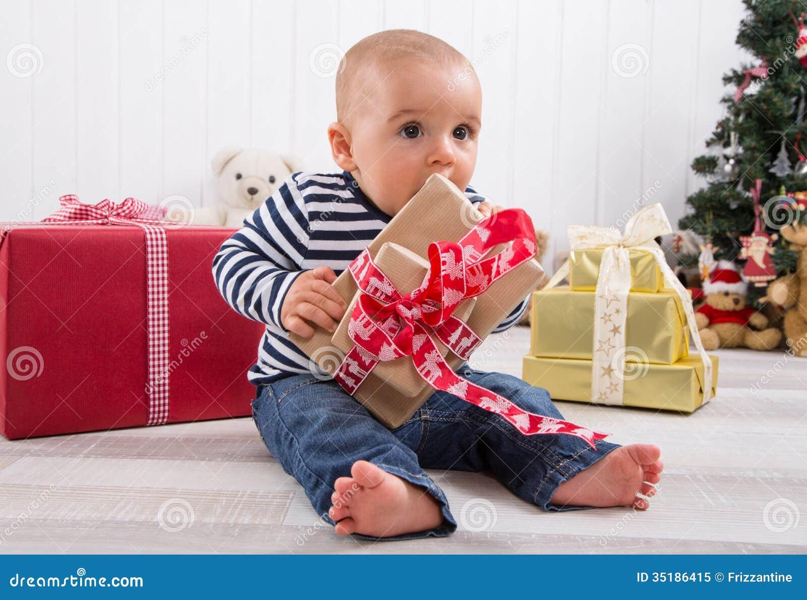 第一圣诞节:解开一个红色礼物-逗人喜爱的l的赤足婴孩