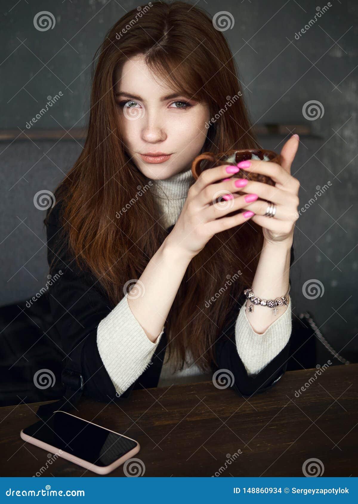 等待在咖啡馆的一名逗人喜爱的俏丽的红头发人妇女的画象享受时间与一个智能手机的咖啡休息在桌藏品工艺