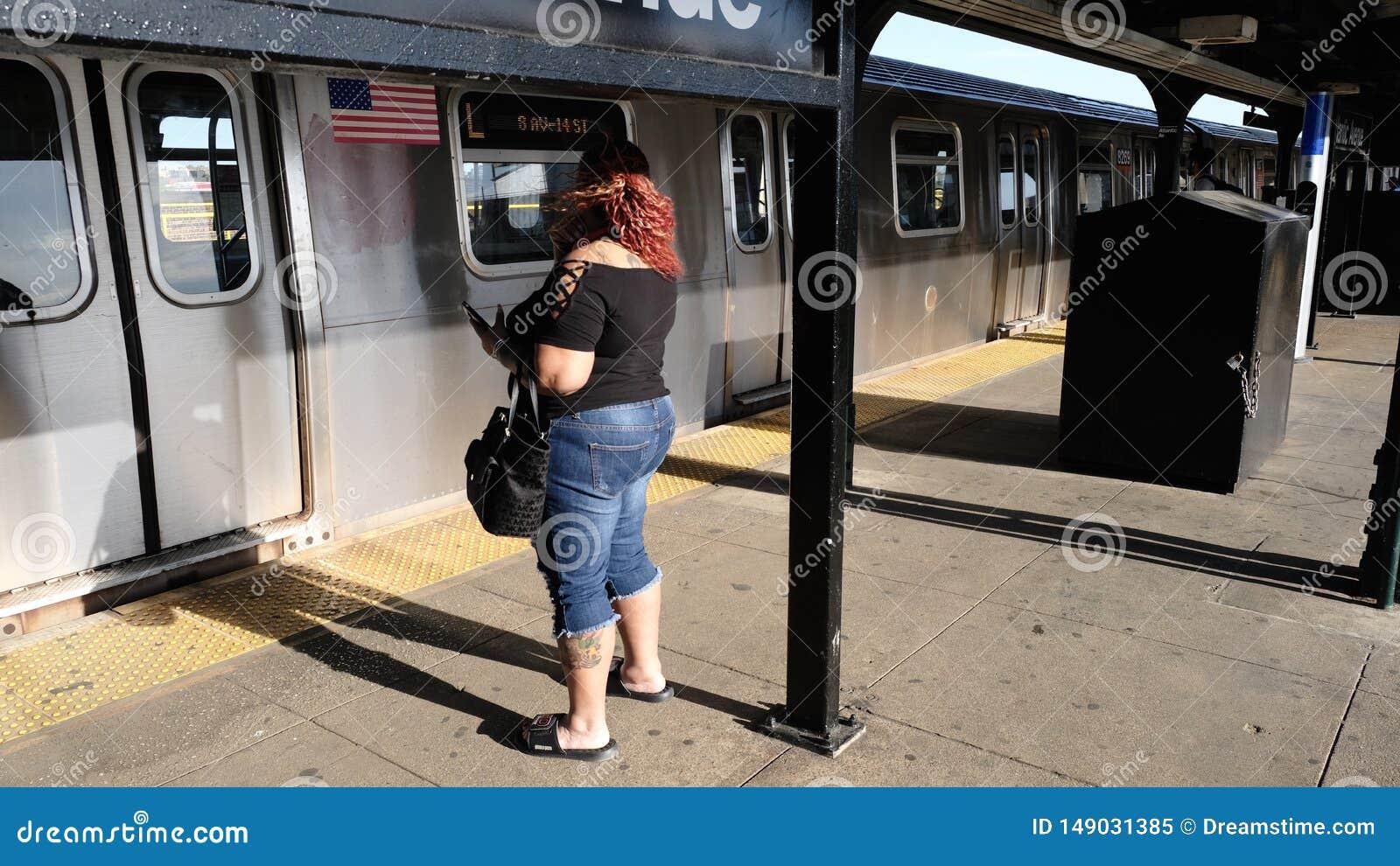 等待在地铁,布鲁克林,NYC的妇女