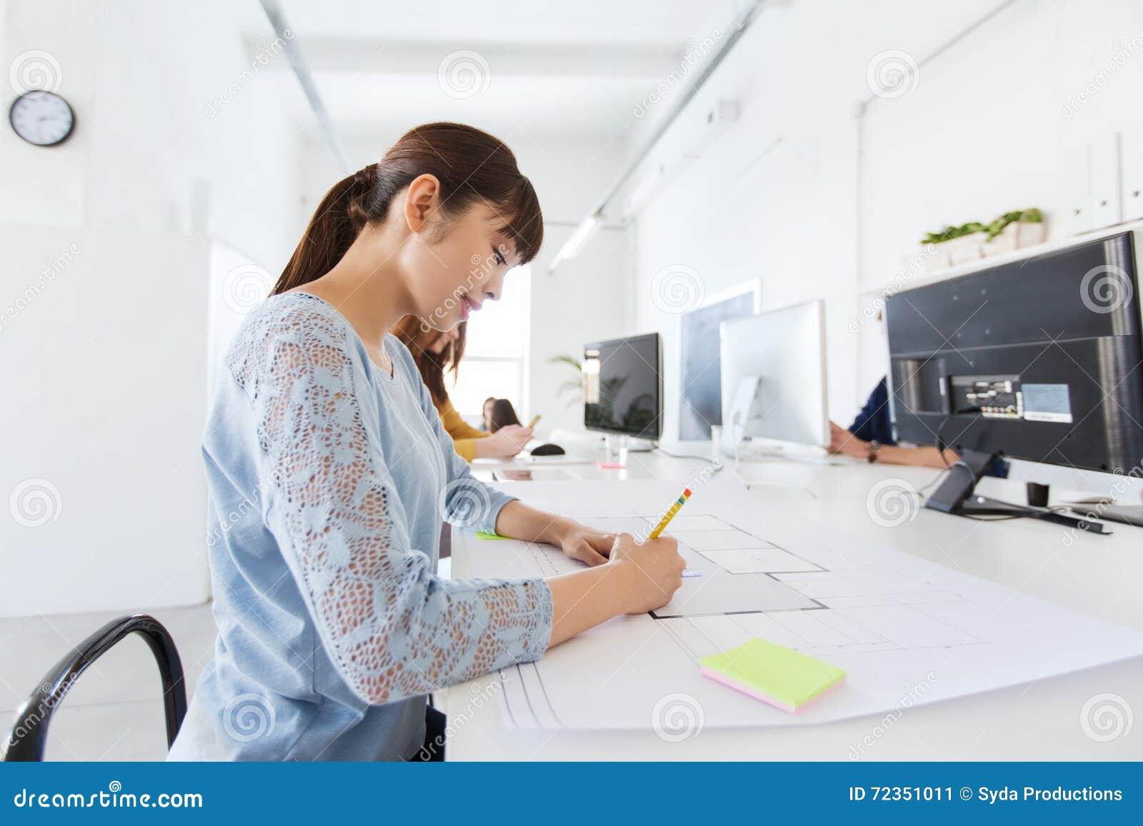 建筑师在图纸的妇女图画在办公室