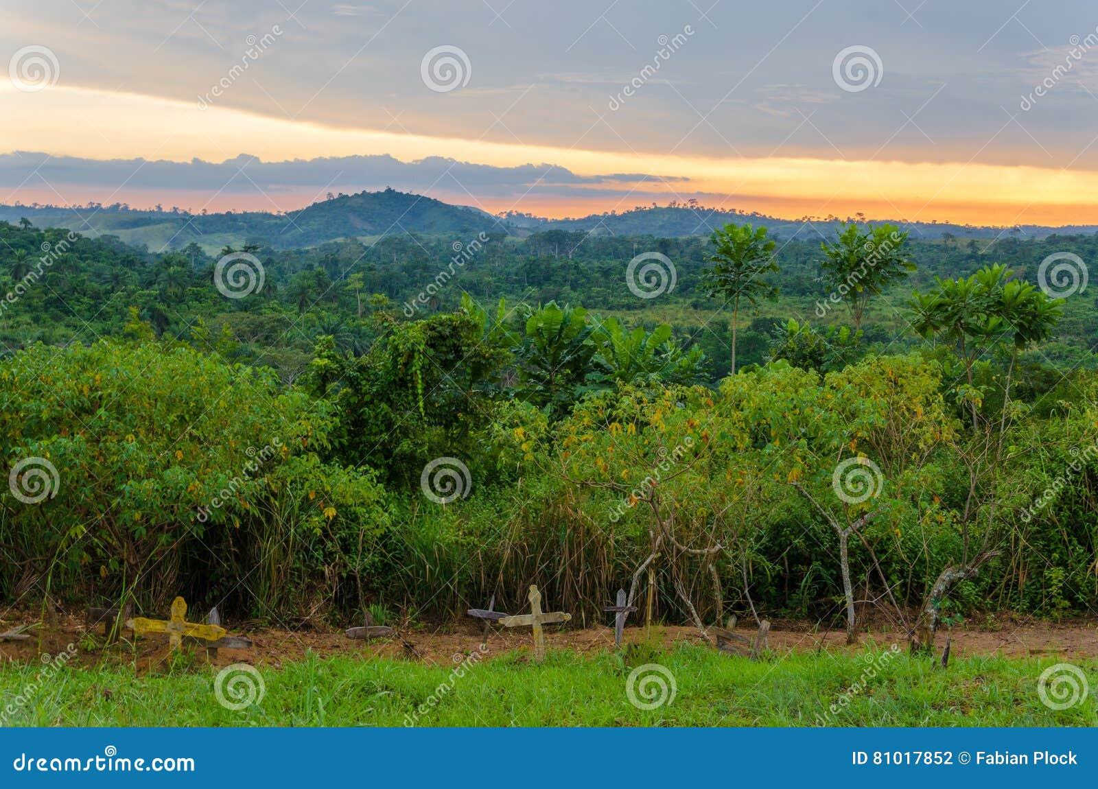简单的木十字架和坟墓在豪华的密林前面和剧烈的日落在刚果