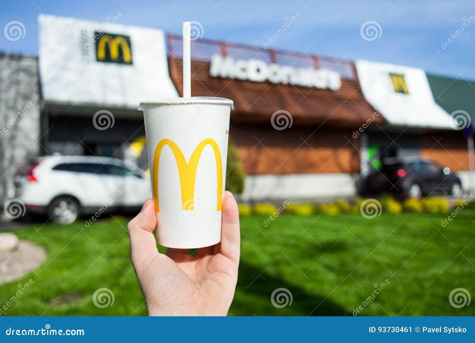 米斯克,白俄罗斯,可以18日2017年:麦克唐纳` s软饮料纸杯有模糊的麦克唐纳` s餐馆背景