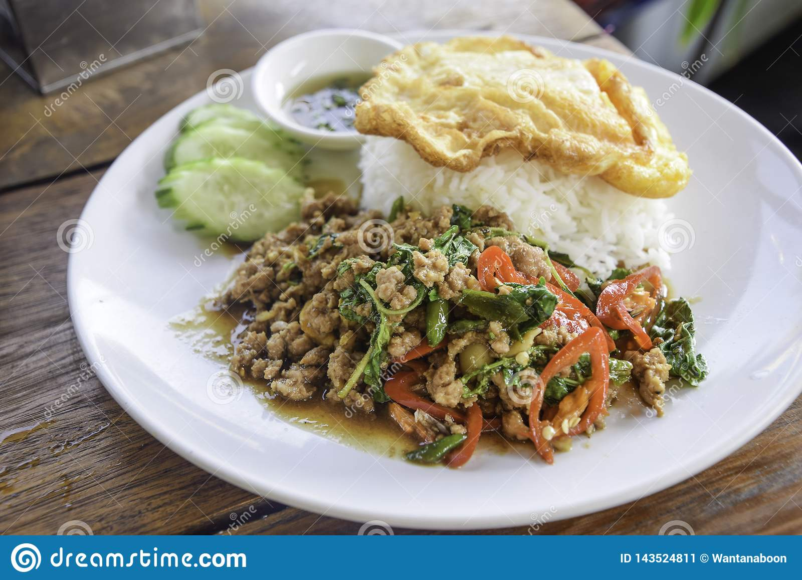 米用与蓬蒿叶子的混乱油煎的猪肉在白色盘