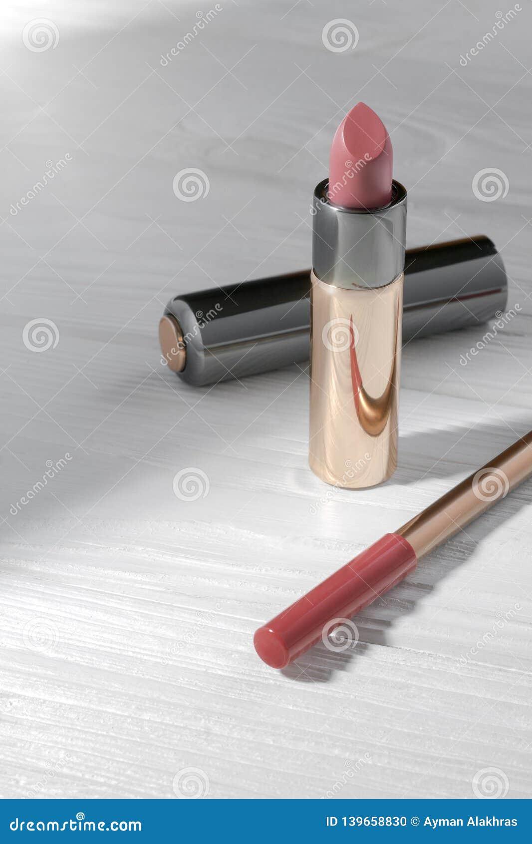 粉色口红和桃红色嘴唇铅笔在木桌上