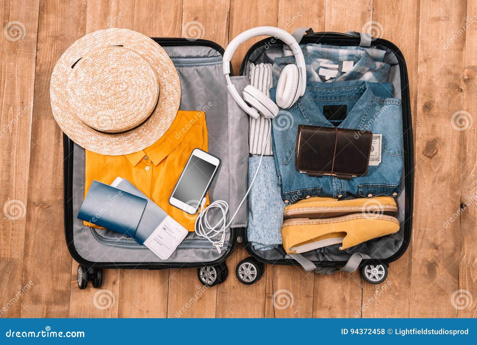 精华顶视图游人的有衣裳、辅助部件和小配件的,钱包,护照,在袋子的智能手机