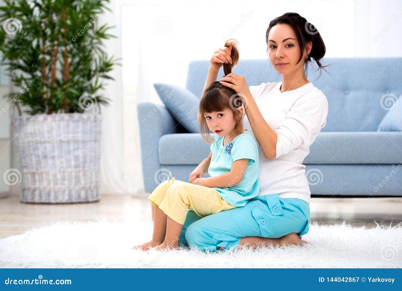 系列愉快爱 母亲在屋子里梳她的女儿的在地毯的头发开会在地板上