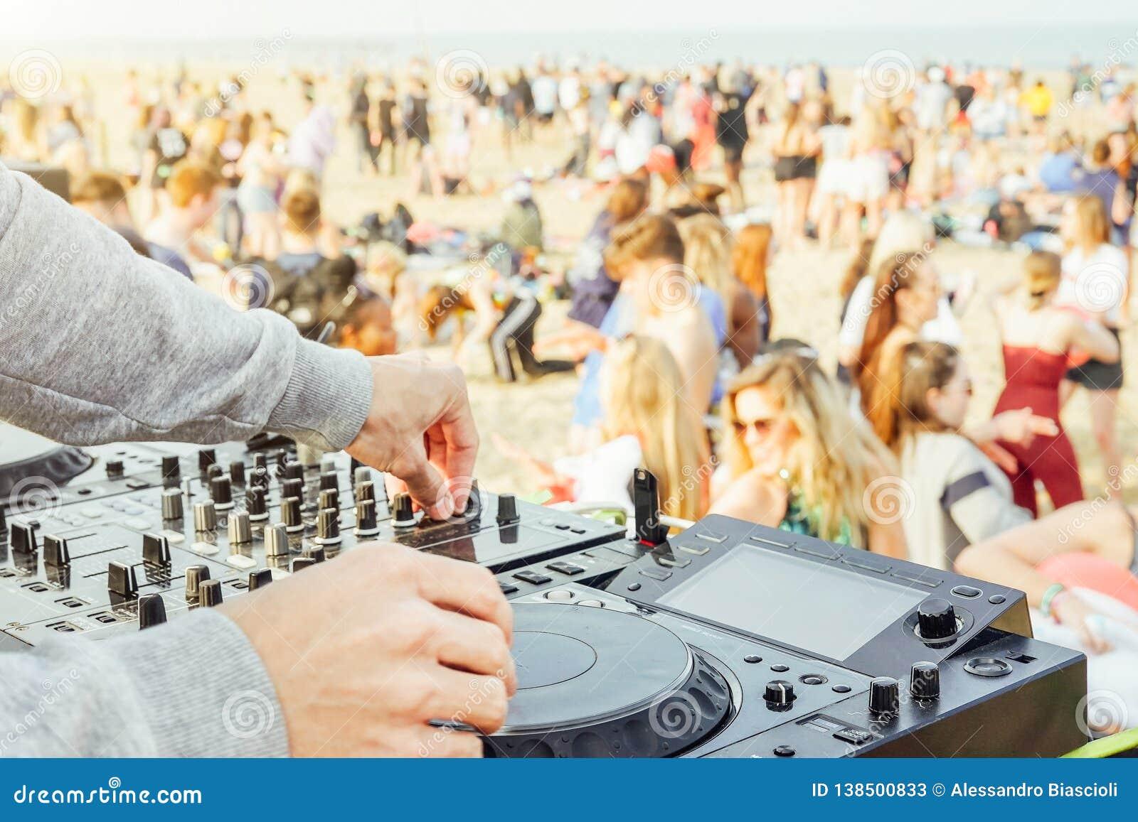 紧密演奏音乐的DJ的手在转盘在海滩党节日-人群人跳舞和有乐趣在室外的俱乐部-