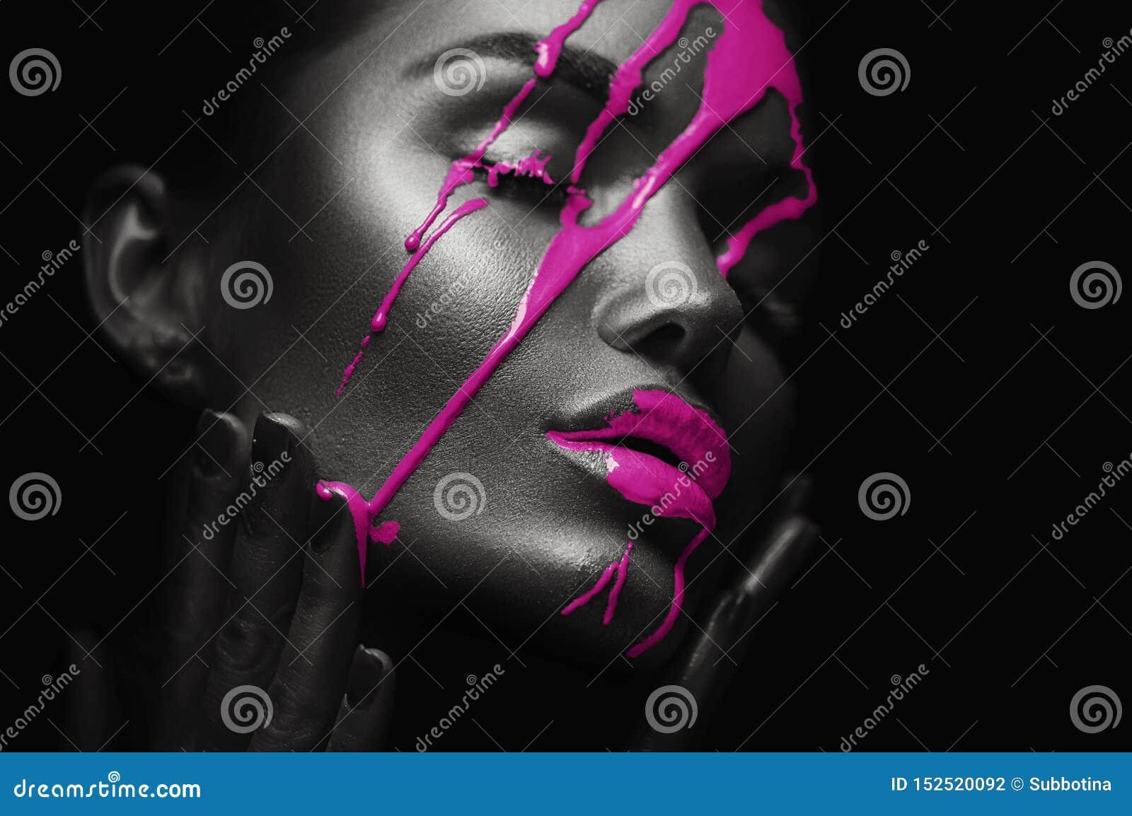 紫色油漆弄脏从妇女面孔的滴水 在美丽的模型女孩的嘴的液体下落 性感的妇女构成