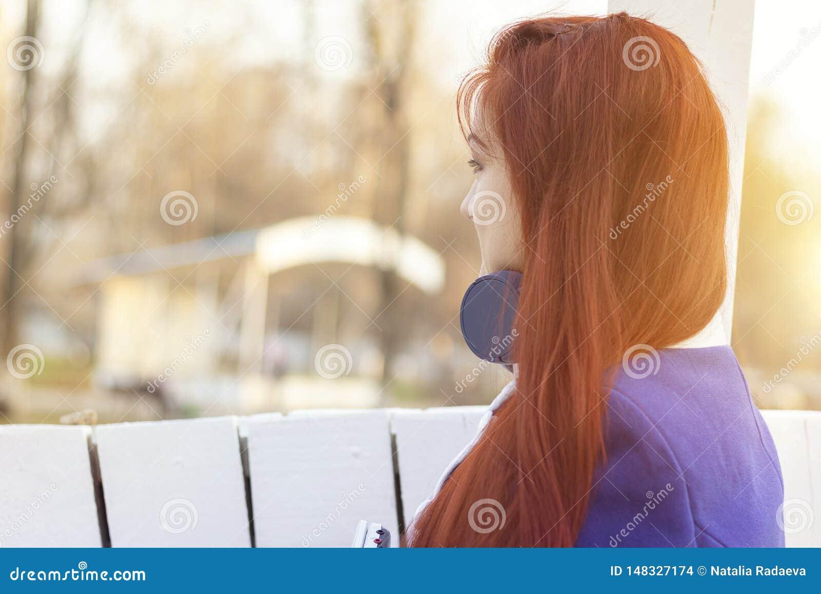 红发女孩,面孔的画象半轮的不是可看见的 有耳机的一年轻女人在春天和秋天在公园