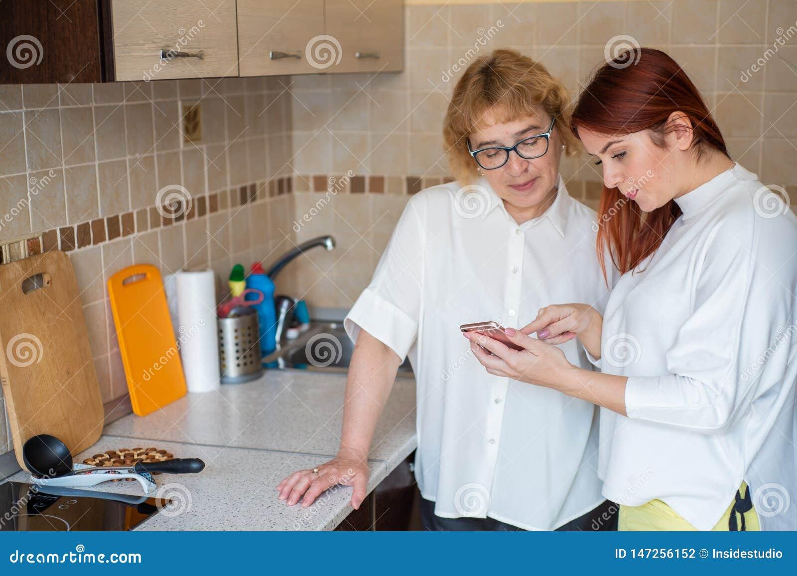 红发妇女教一个年长母亲如何使用智能手机 在白色女衬衫和成人女儿打扮的母亲
