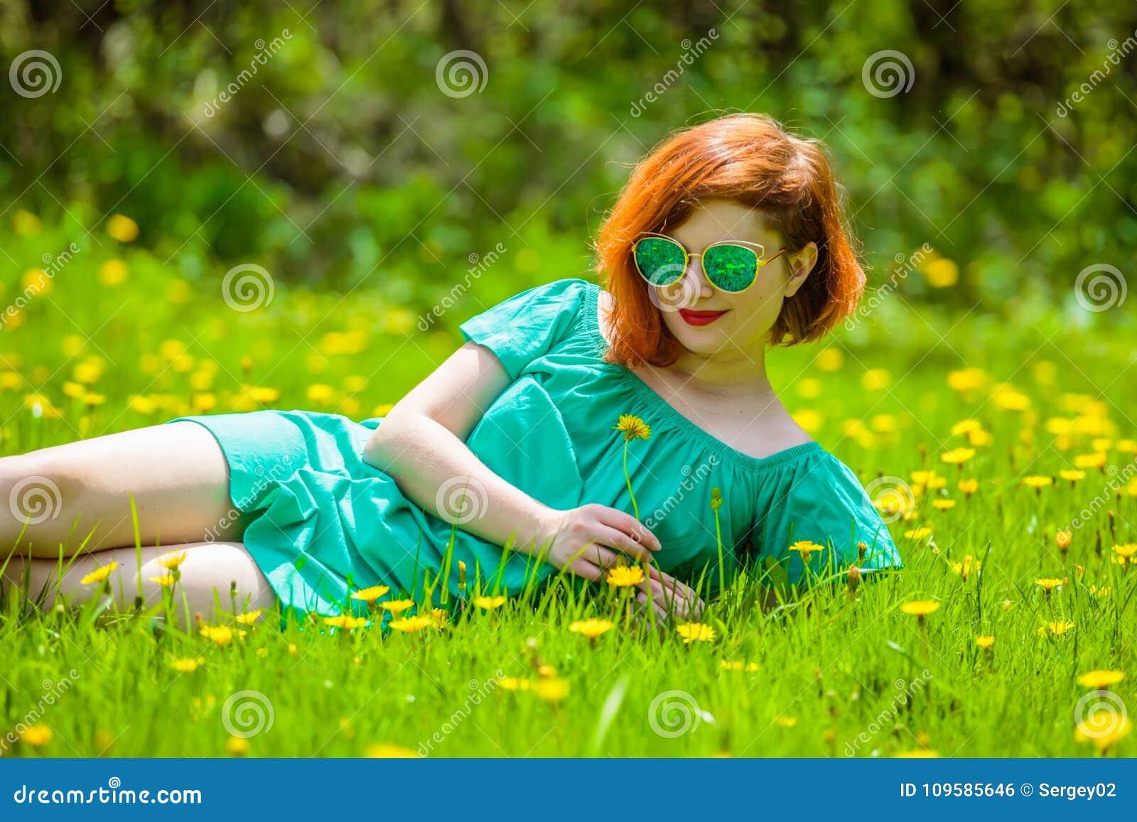 红头发人少妇画象放松在春天公园的