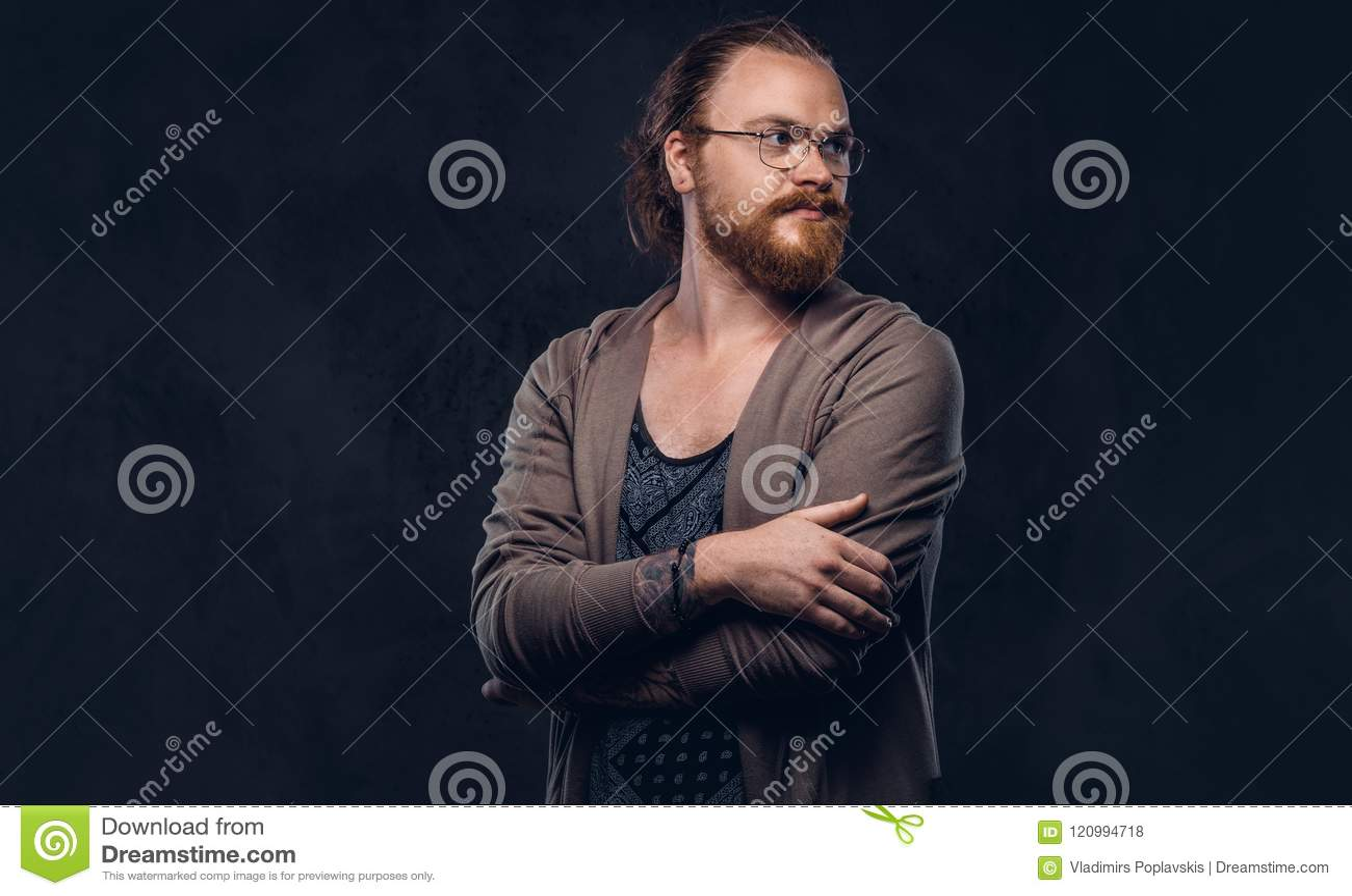 红头发人行家男性的画象在有玻璃和充分的胡子的便衣穿戴了,站立与横渡的胳膊