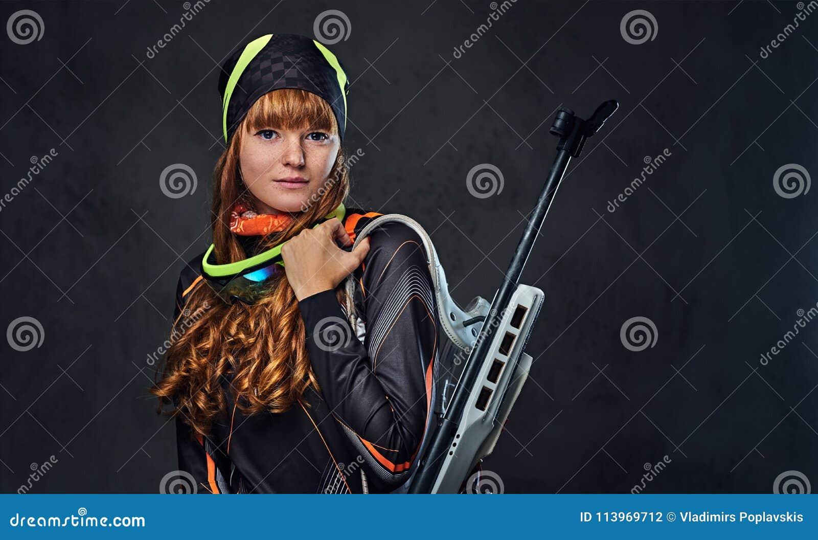 红头发人Biatlon女性运动员举行竞争枪