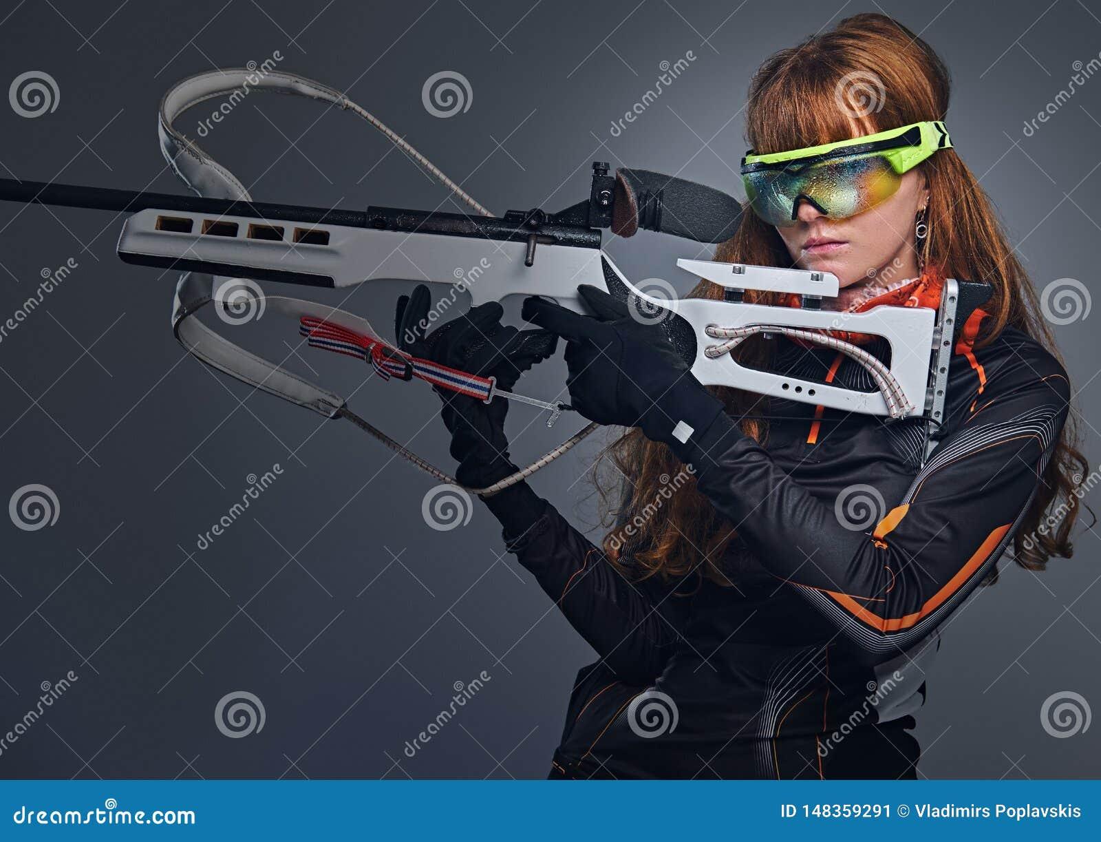红头发人Biatlon女性运动员拿着竞争枪