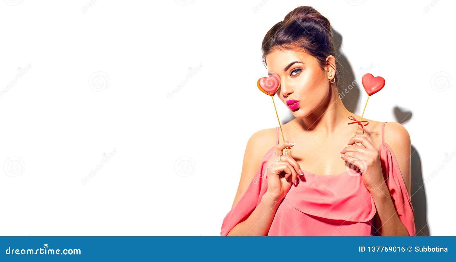 红色上升了 秀丽快乐的年轻时装模特儿女孩用华伦泰心形的曲奇饼在她的手上