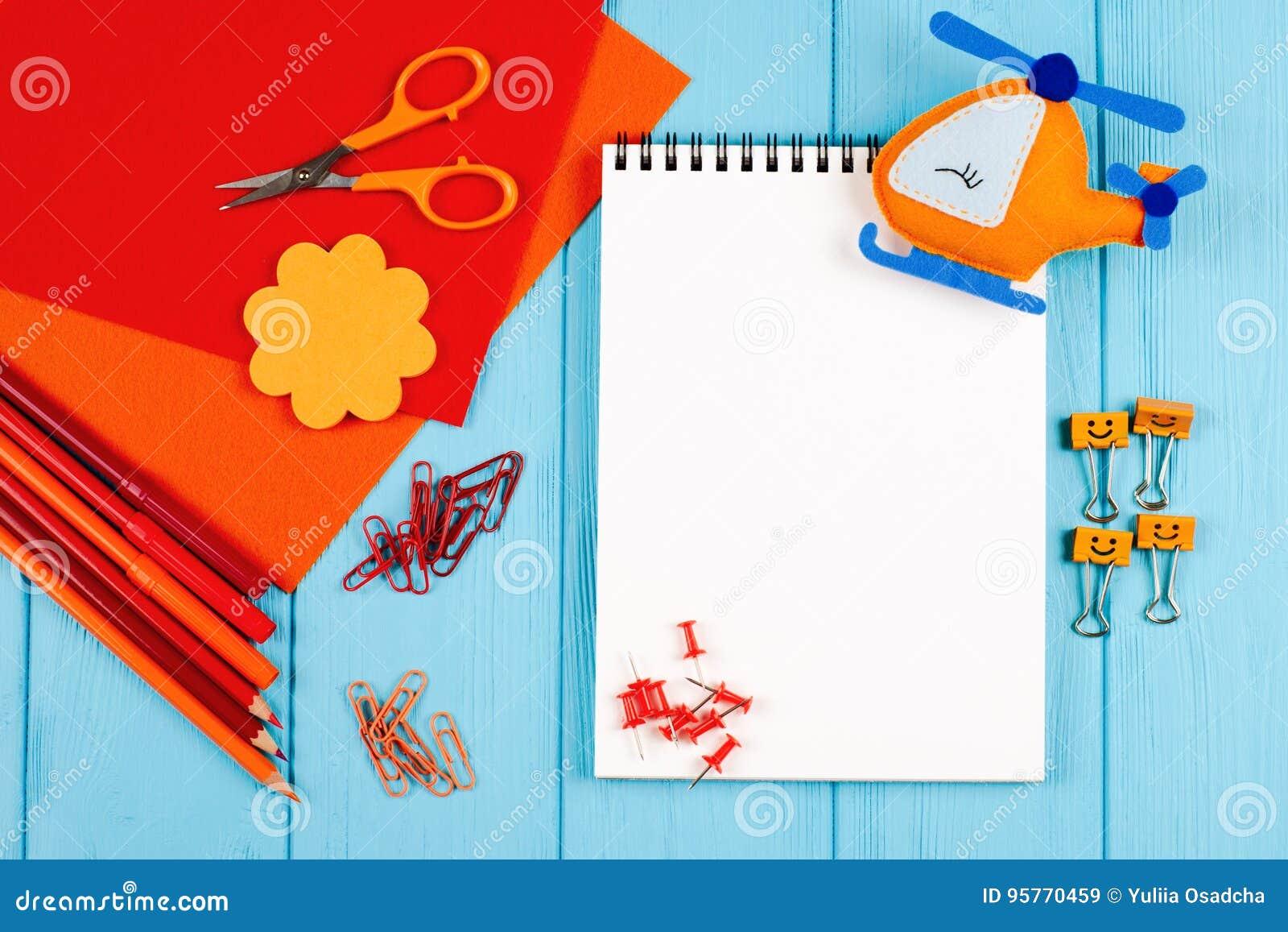 红色和橙色铅笔、毡尖的笔、便条、纸夹、文具钉子、毛毡和剪刀在蓝色木背景