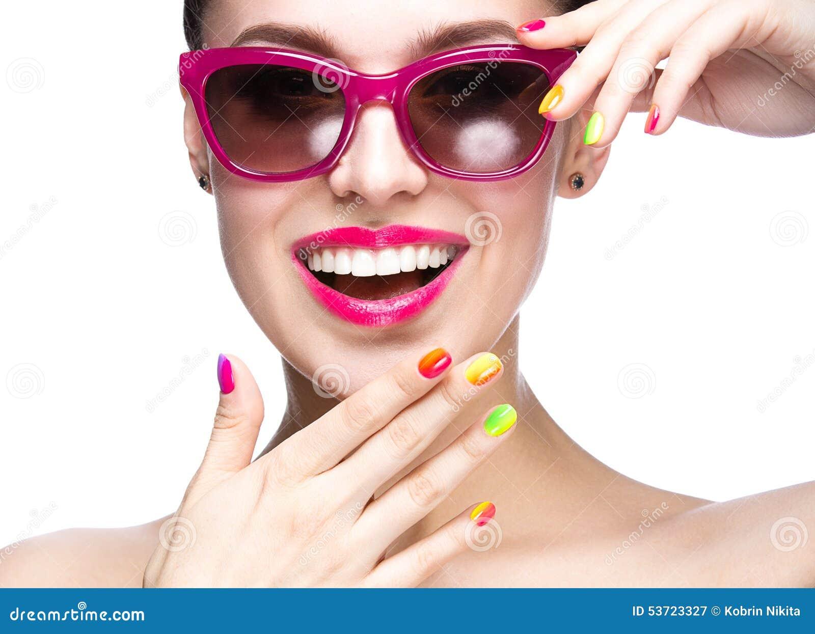 红色太阳镜的美丽的女孩有明亮的构成和五颜六色的钉子的 秀丽表面
