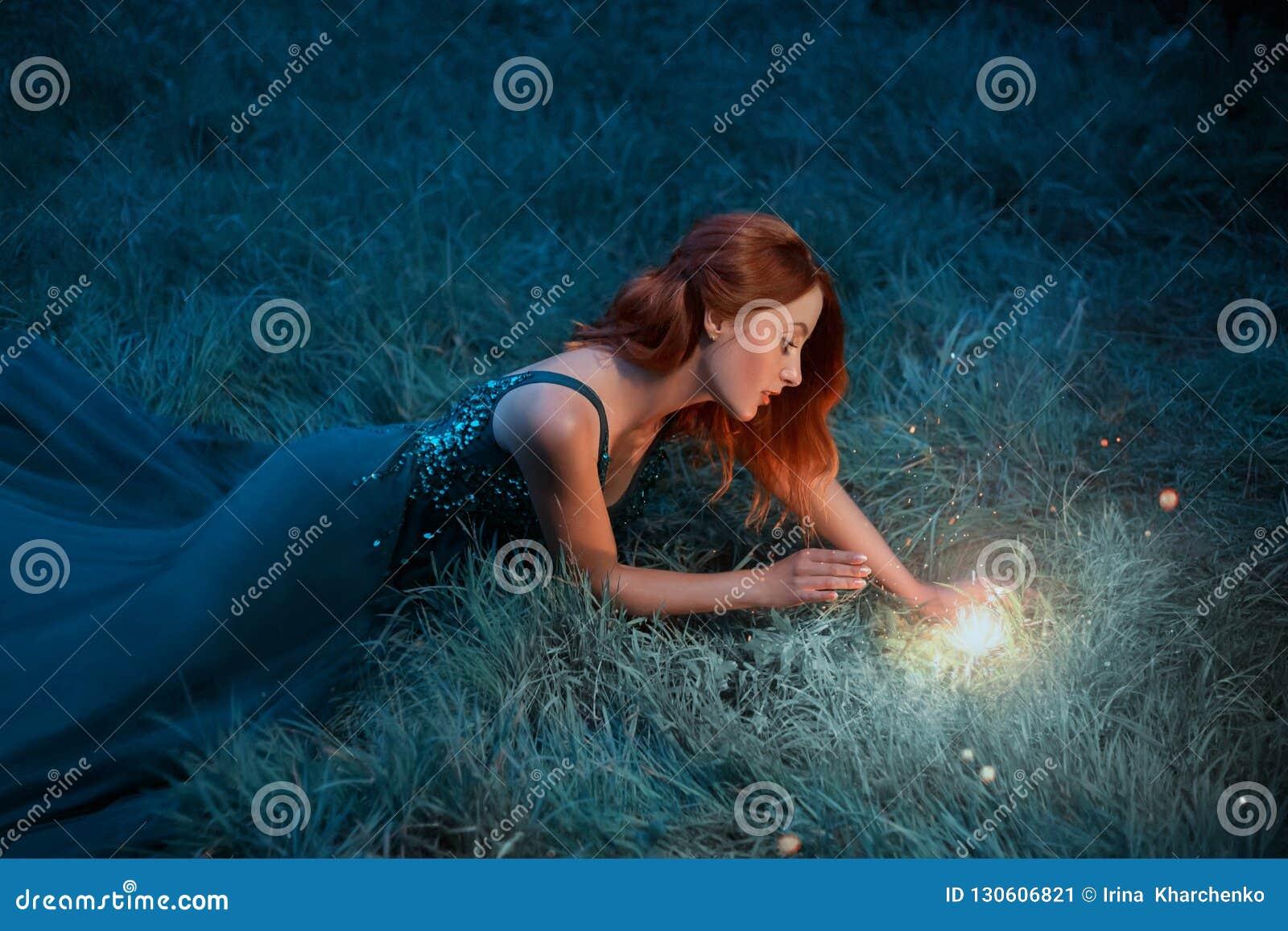 红色头发年轻女人在一件美妙的礼服的草说谎有长的火车的