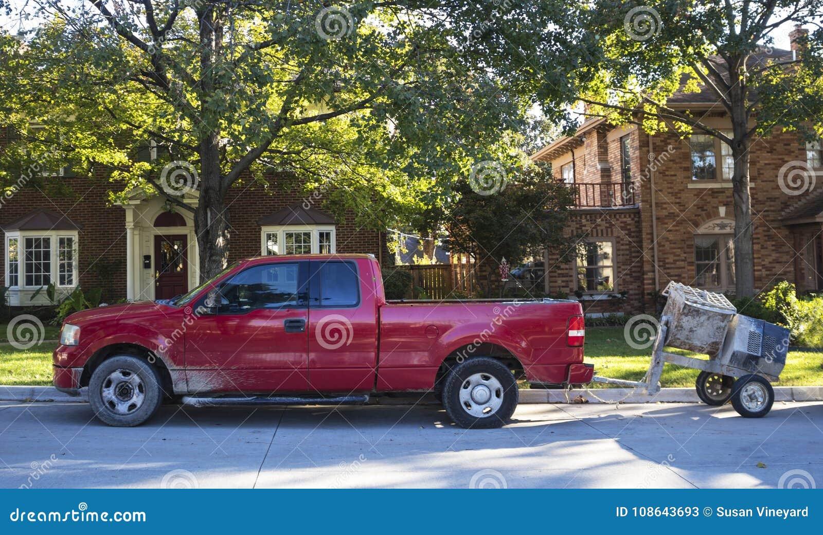 红色工作在传统邻里拾起有在街道上停放的水泥搅拌车的卡车