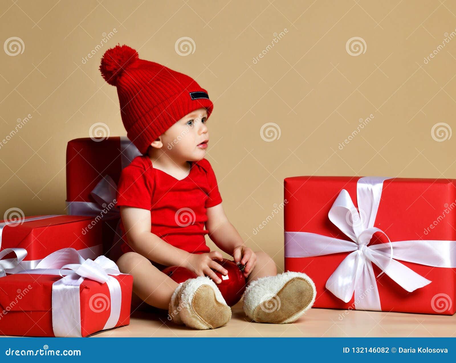 红色帽子的孩子有堆的在的当前箱子坐地板附近